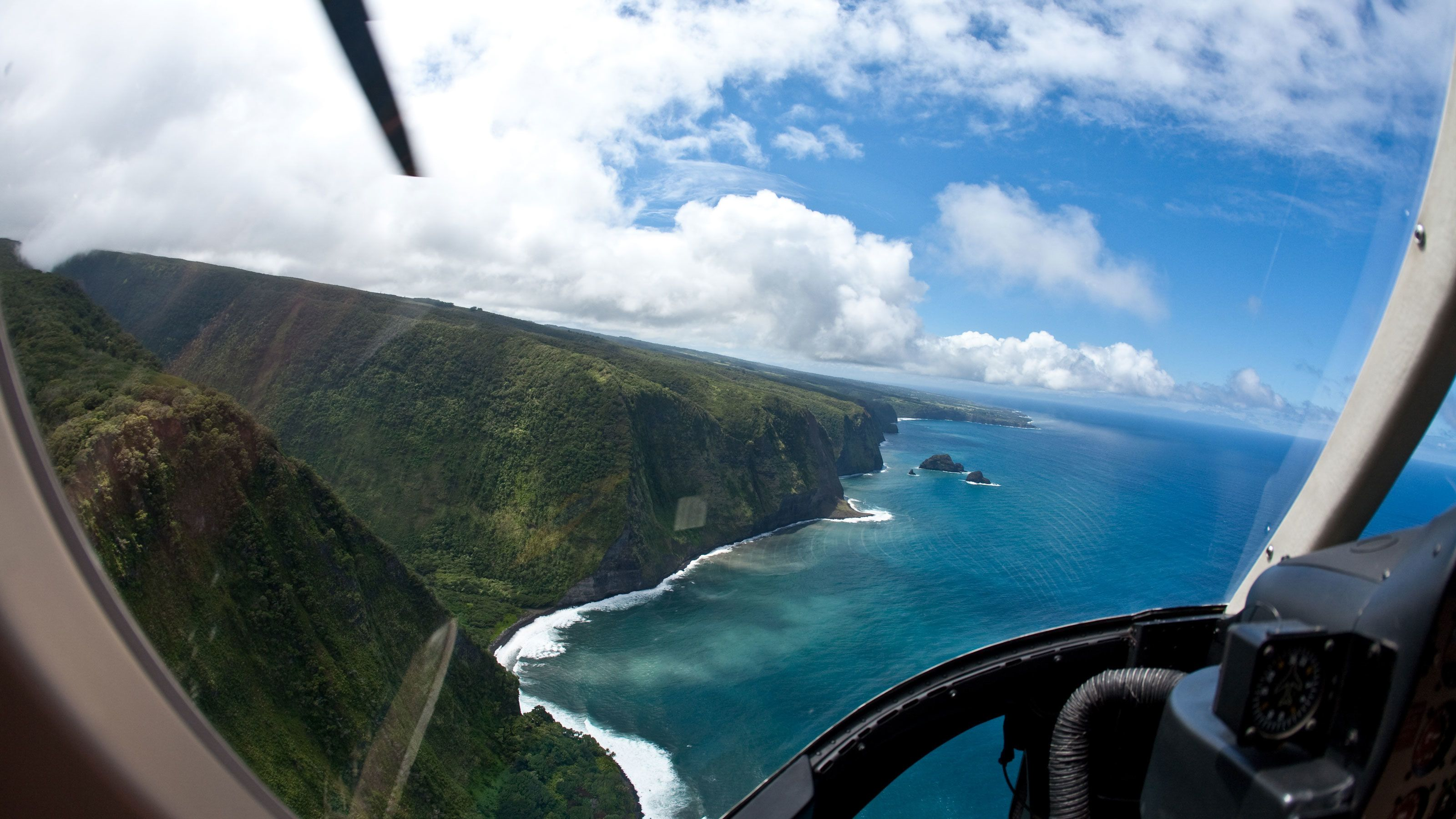 Helicopters pilots point of view over the cliffs on the shore line in Hawaii