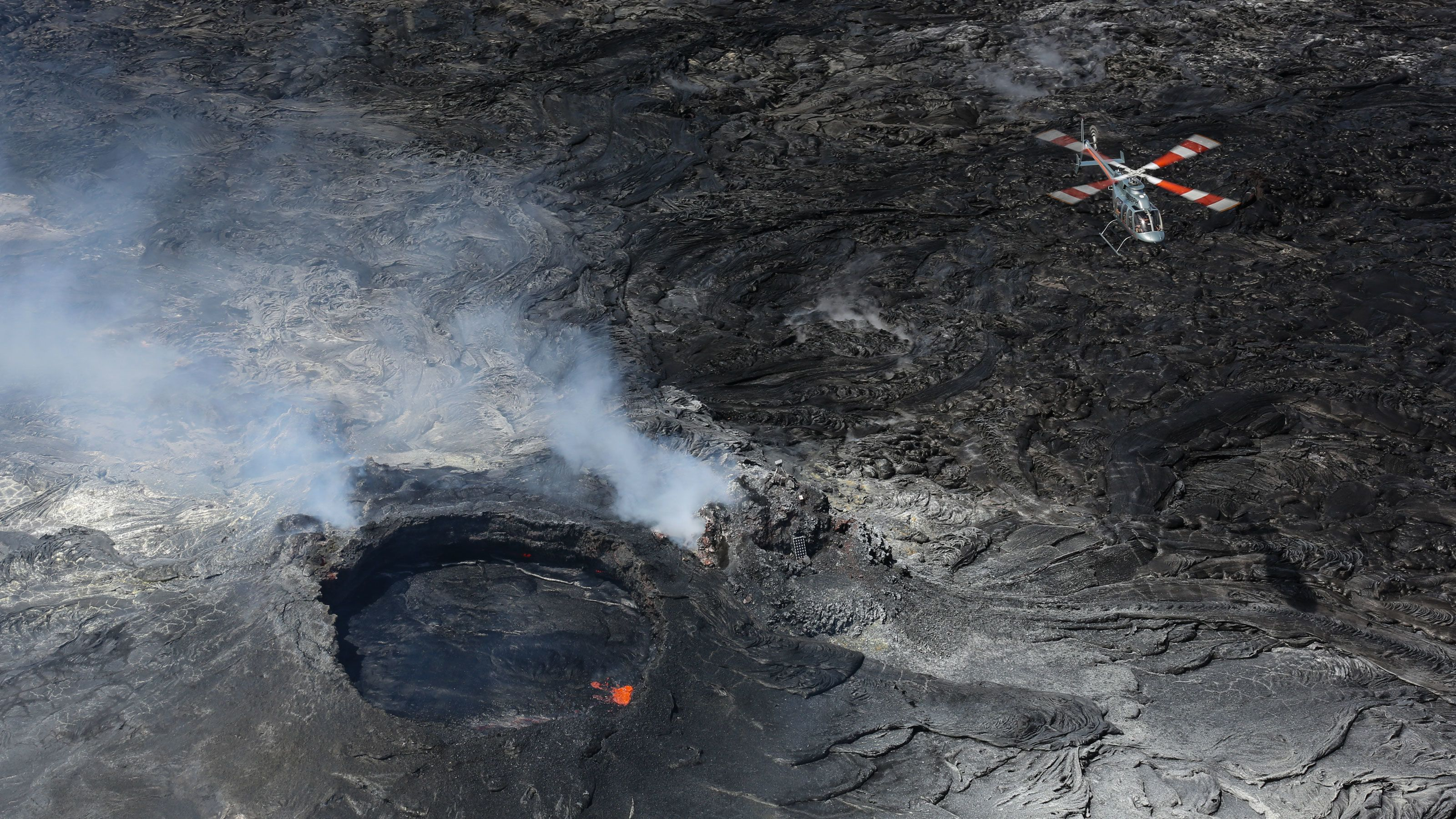 Helicopter flying over a smoking volcano in Hawaii