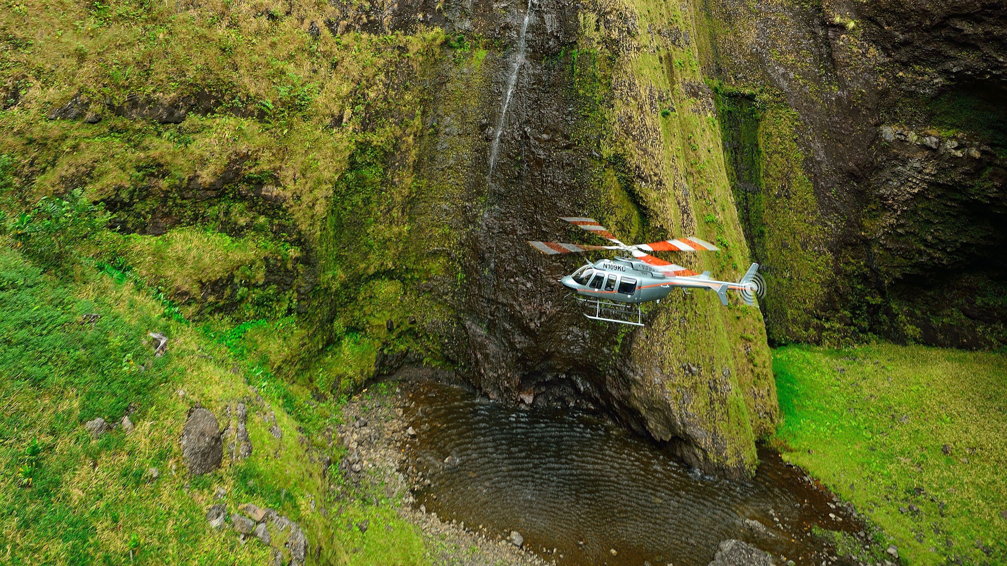Helicopter flying near waterfall in Hawaii
