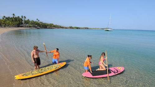 Instructors helping couple with paddle boarding