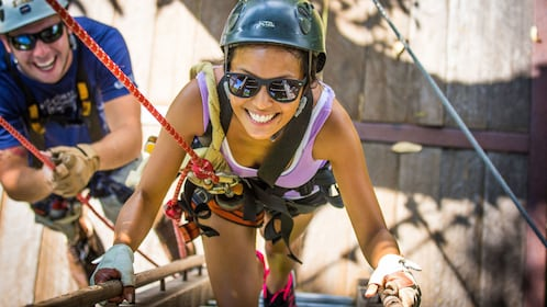 Woman climbing up stairs to go zipling in Maui