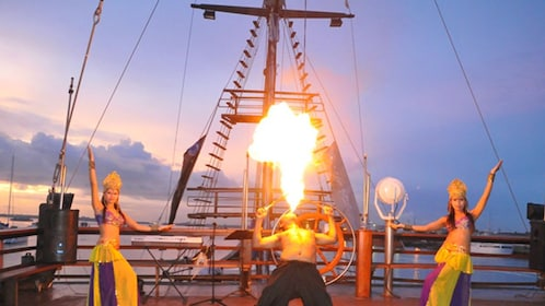 Live entertainment on boat featuring fire blower and dancers.
