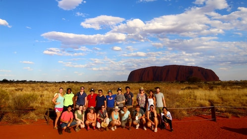 Tour group posing for a photo with Uluru in the background