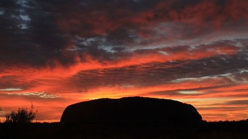 Silhouette of dome-shaped Uluru rock at sunset