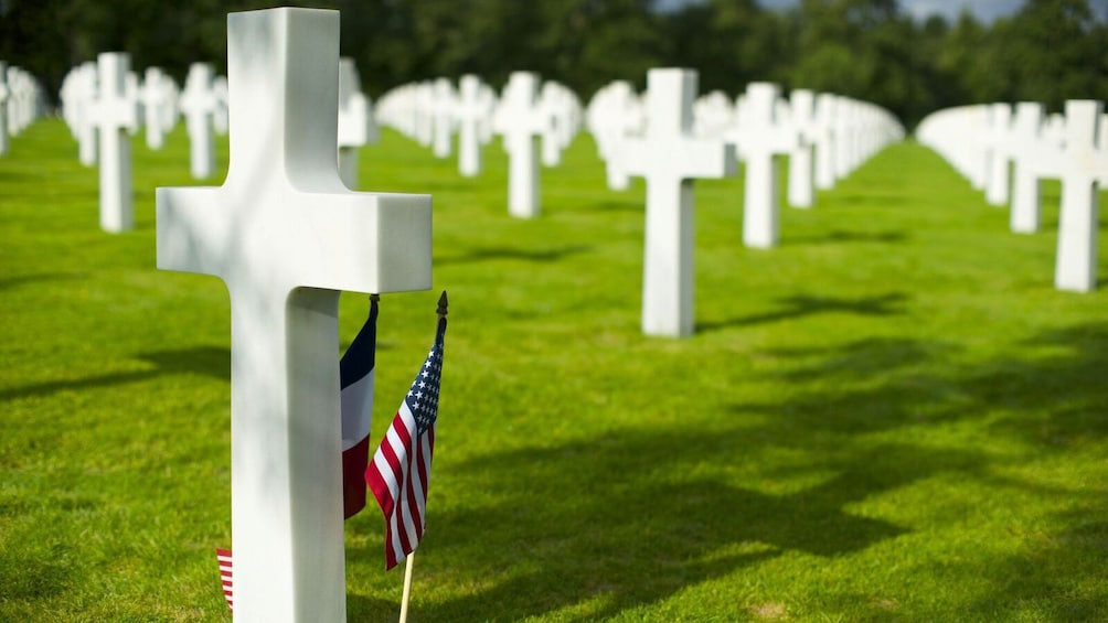 rows of white crosses with american flag