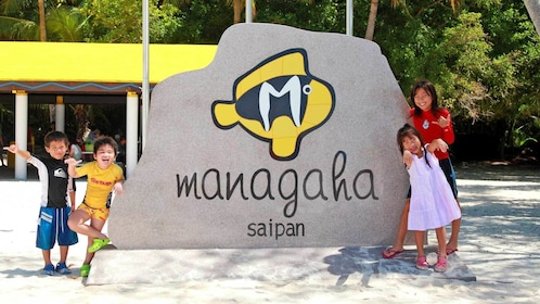 children hanging around the Managaha sign in Micronesia