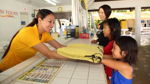 staff handing beach towel to a child in Micronesia