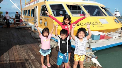 children near a docked boat at the bay in Micronesia