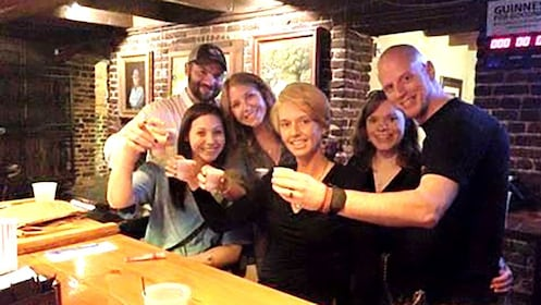 A group of people on a ghost tour toast at a ba