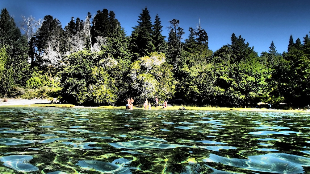 Crystal clear waters of San Carlos de Bariloche with swimmers on the shore
