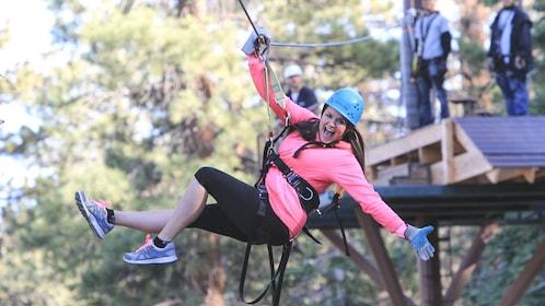 Smiling woman moving down zipline with helmet.