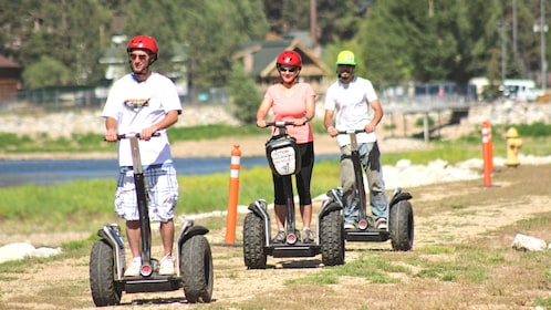 Group riding down dirt path on segways with helmets.