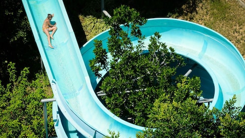 A woman slides down a curly waterslide.