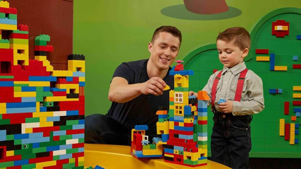 Show item 10 of 10. A father and son play in Lego Land.