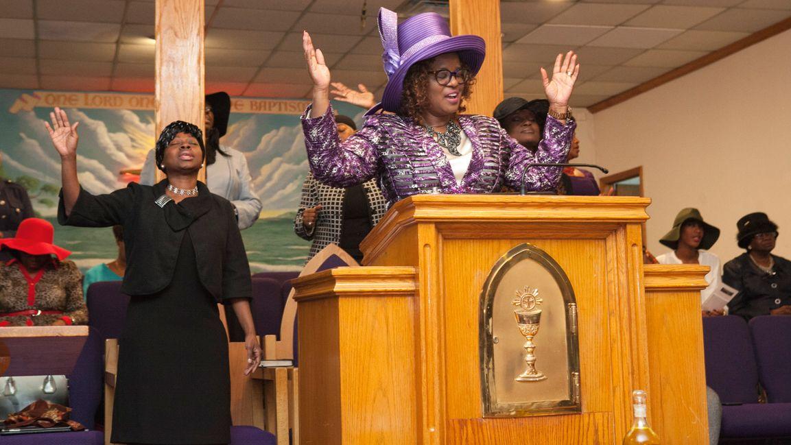 Woman at podium in worship during church service.