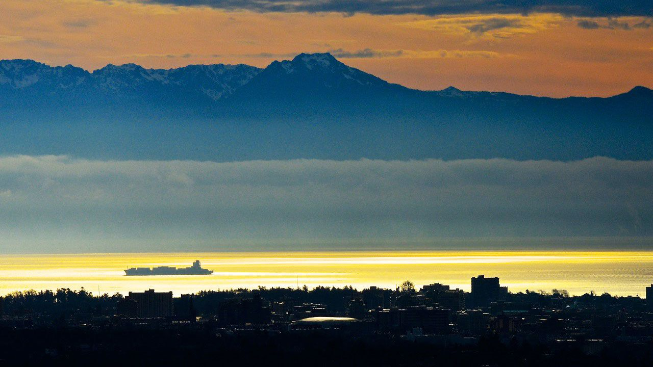 Cargo ship in the bay with mountains in background and city view at twilight in Vancouver