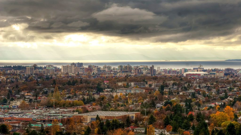view of cityscape of Vancouver with sun breaking through the clouds.