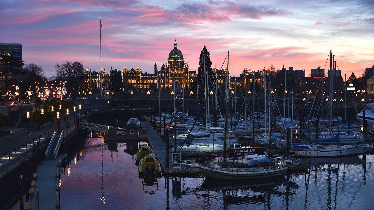 Parliament building decorated with lights, marina with boats in foreground at twilight in Vancouver