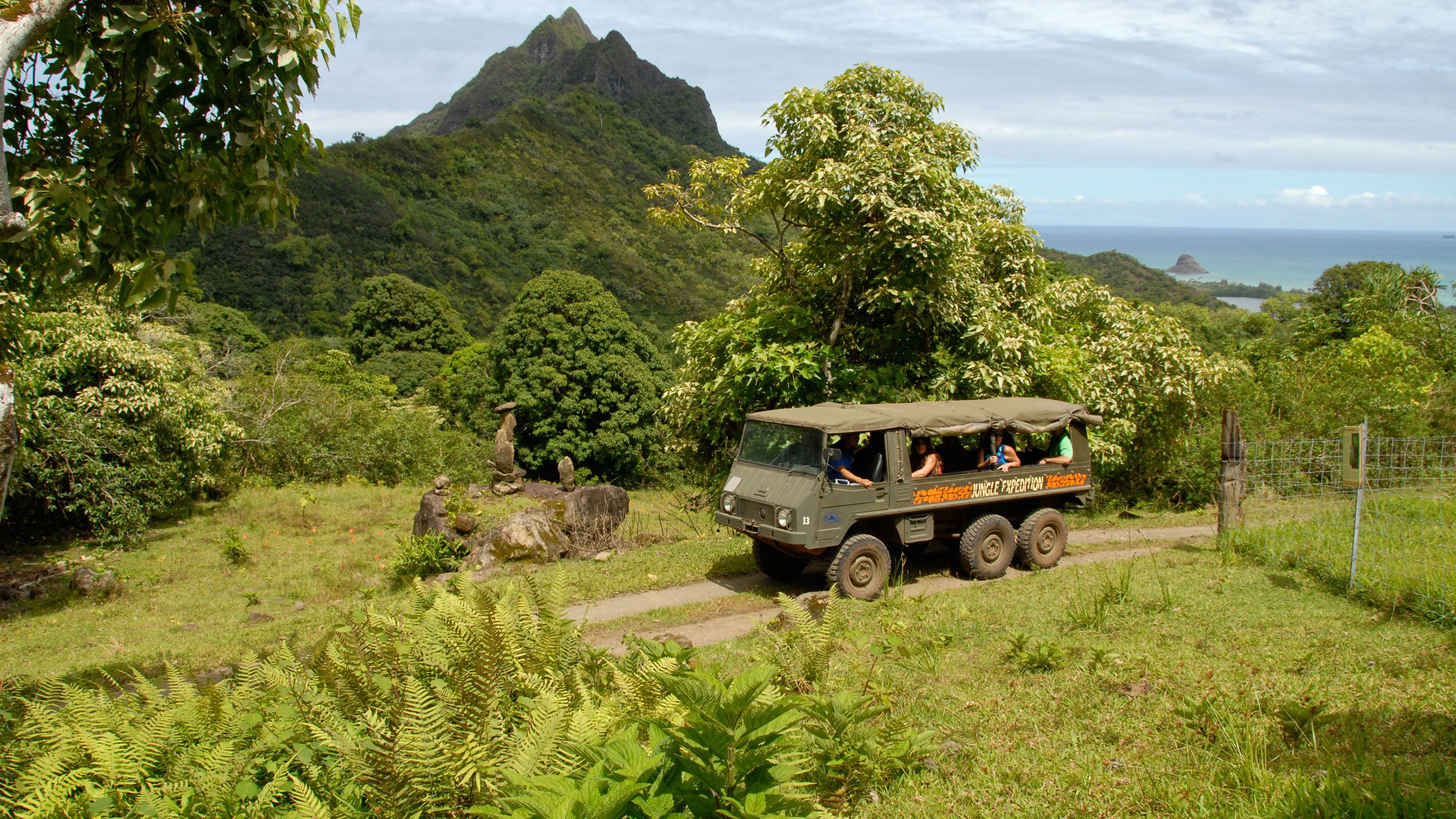 Touring vehicle with mountains in the background on Oahu