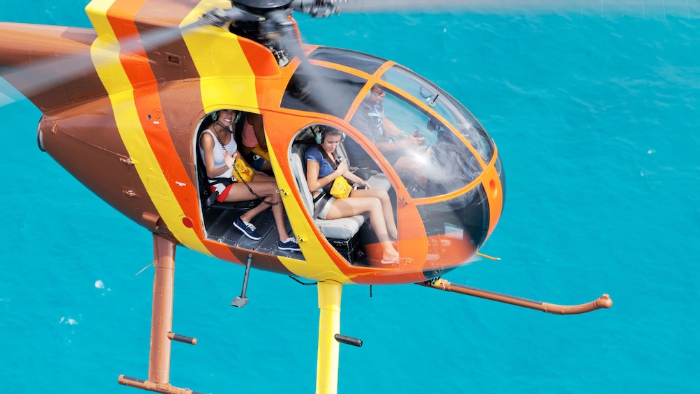 Show item 3 of 9. Helicopter with doors off flying on a sunny day in over the waters in Oahu