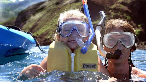 Mom and daughter snorkeling near their kayak in Maui