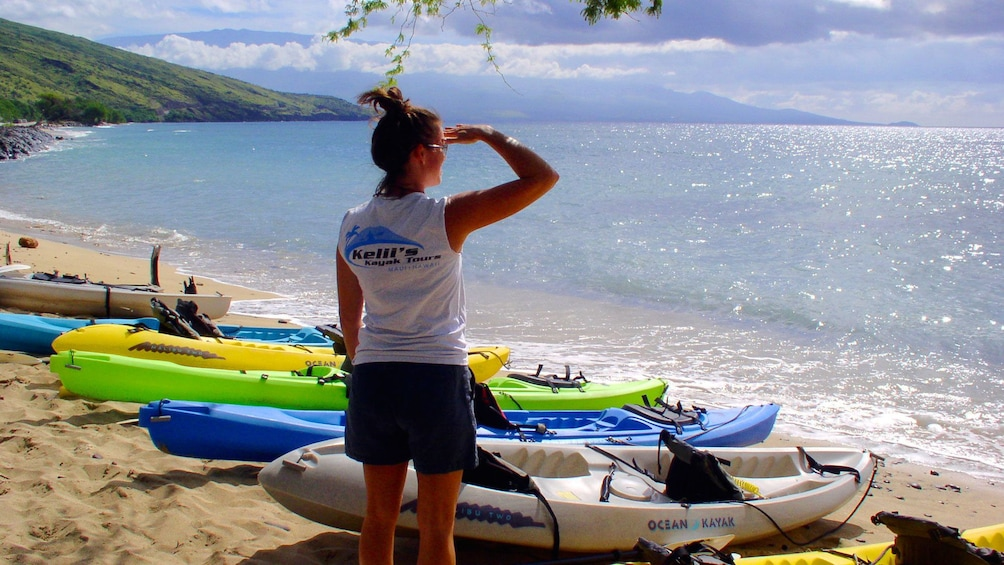 Show item 5 of 7. Woman looking out at ocean with kayaks beached on sand in Maui