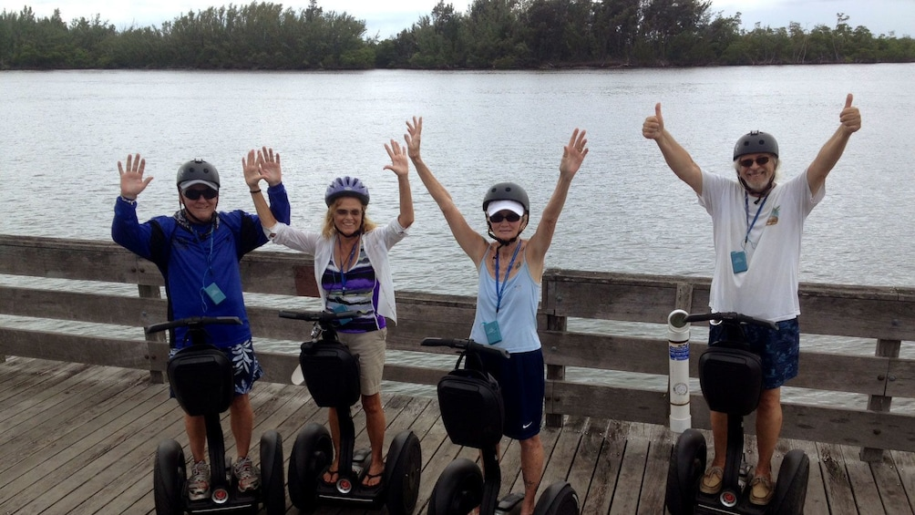 Show item 3 of 5. Group of segway riders on a path along the water in Florida