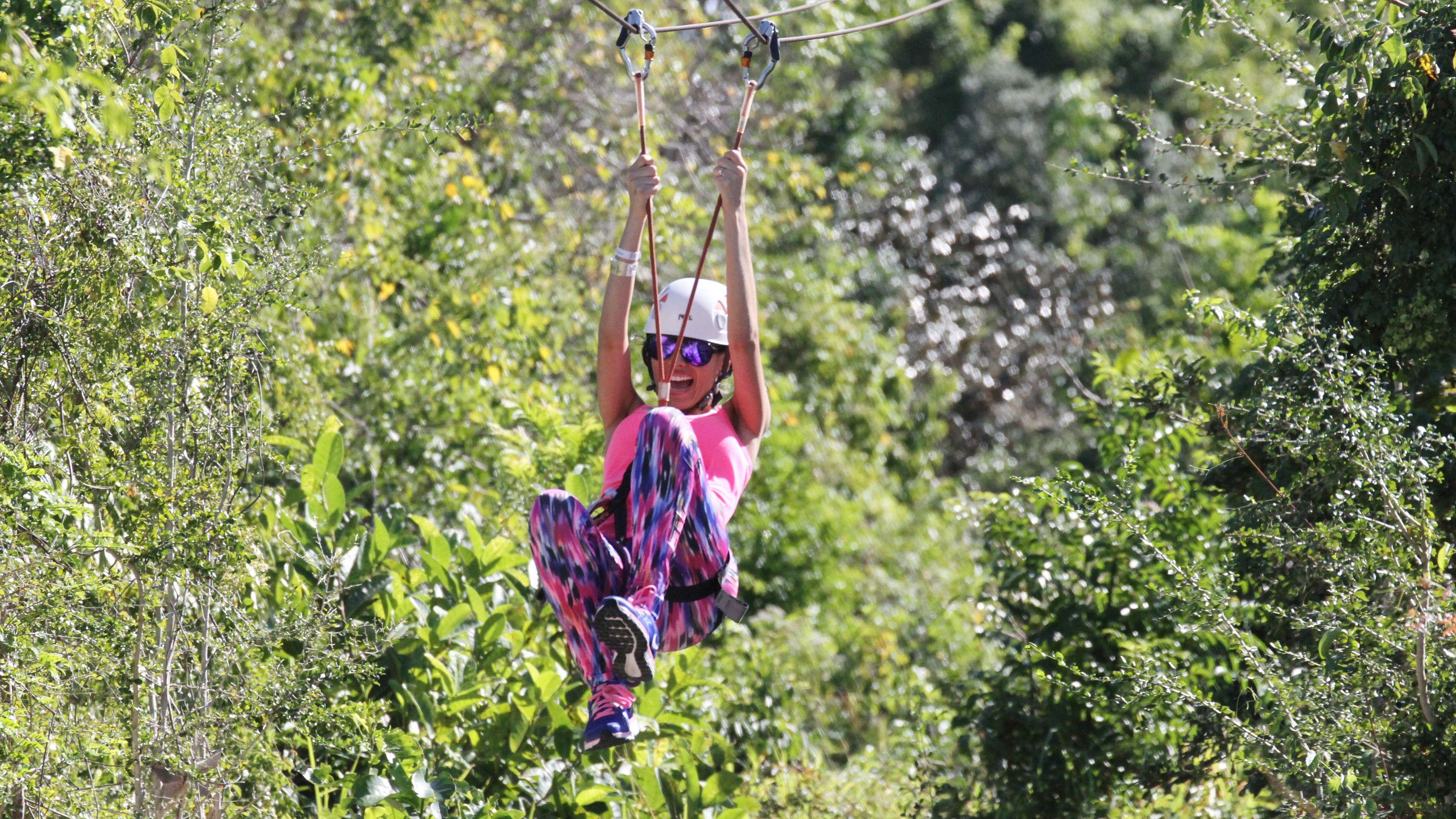 woman zip lines through trees at theme park in Santo Domingo