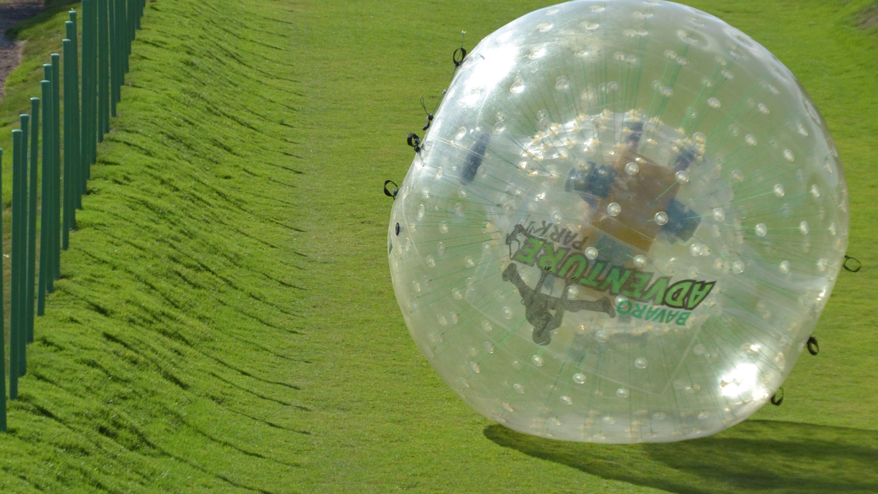 person inside plastic bubble rolling down hill at theme park in Santo Domingo