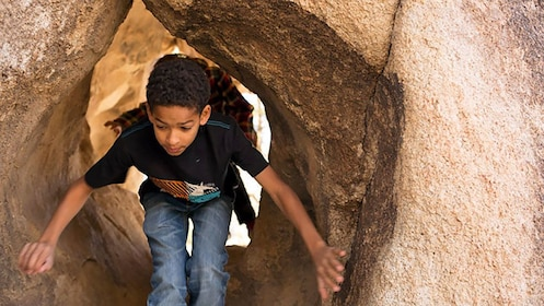 boy walking through a naturally shaped tunnel in Palm Springs