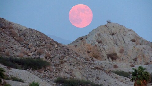 Red moon over the hills at dusk in Palm Springs