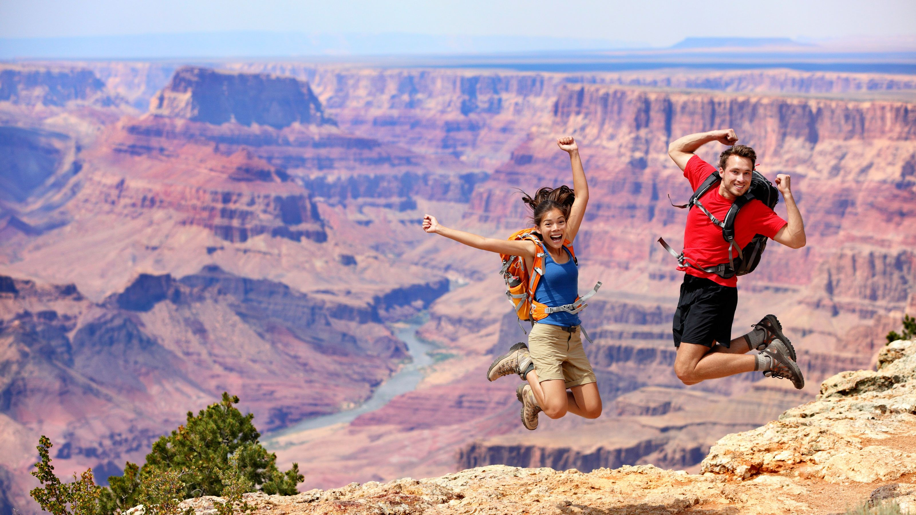 Couple jumping for joy while basking in the majestic views of the Grand Canyon