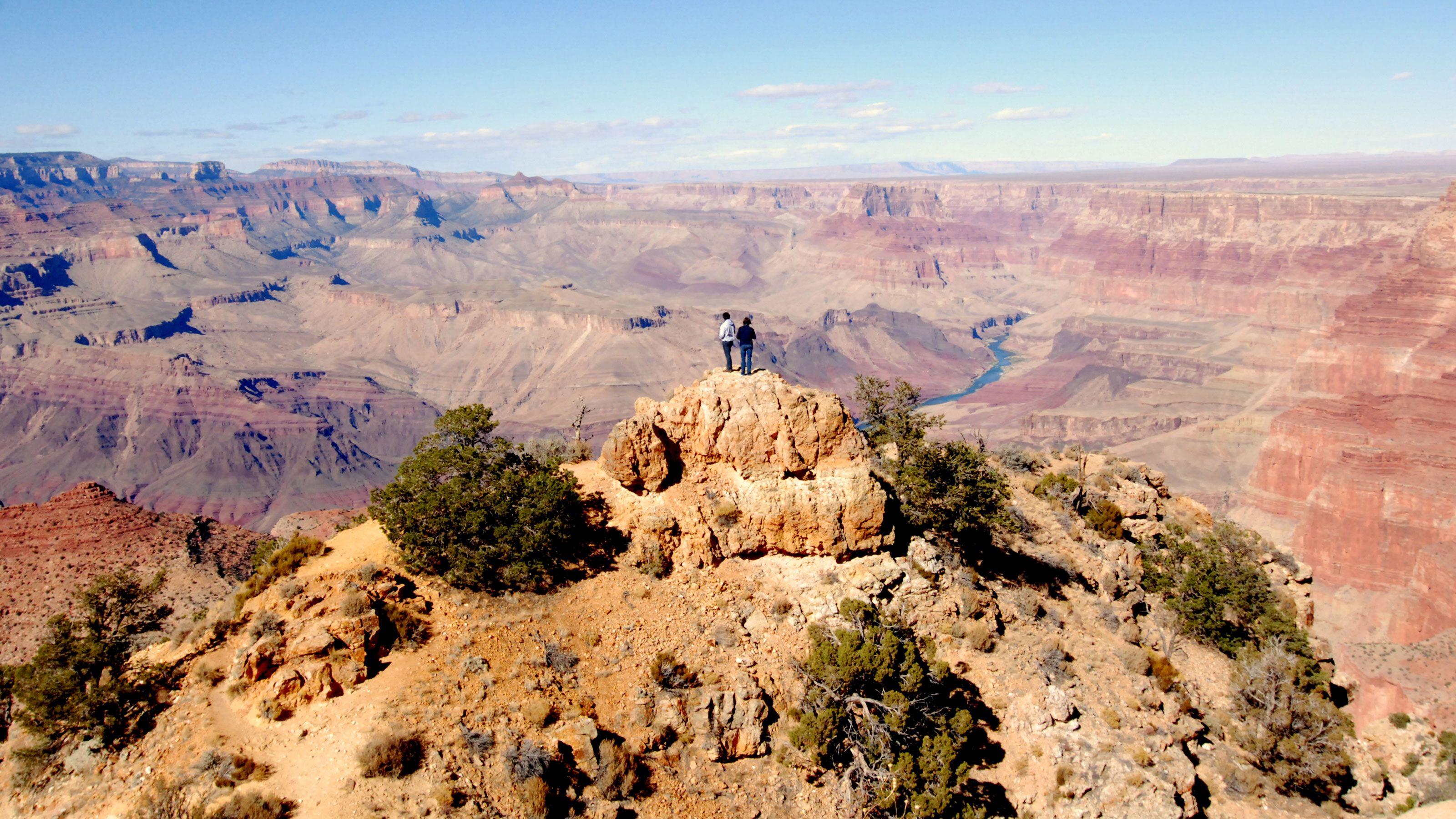 Couple enjoying panoramic views of the Grand Canyon South Rim