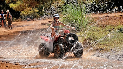 woman riding quad bike through sprinklers in Marmaris