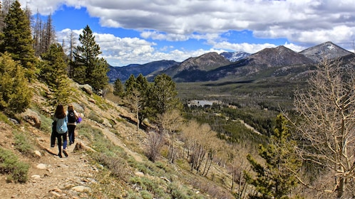 Two women walk a trail in the Rocky Mountains
