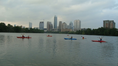 Kayakers in river with view of skyline.