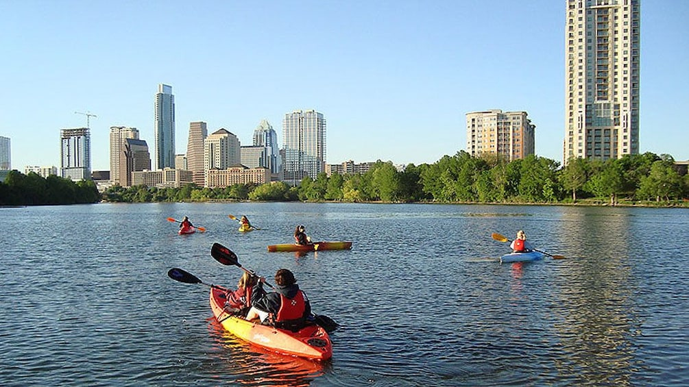 Show item 2 of 8. Several kayakers paddling through river in Austin