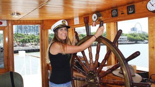 Woman at the helm of the boat in Brisbane