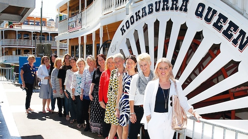 Group stand next to cruise boat in Brisbane