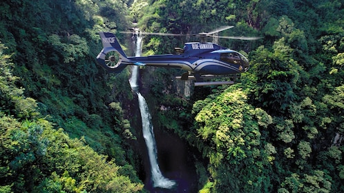 Aerial of helicopter flying near a waterfall in the Hana Rainforest in Maui