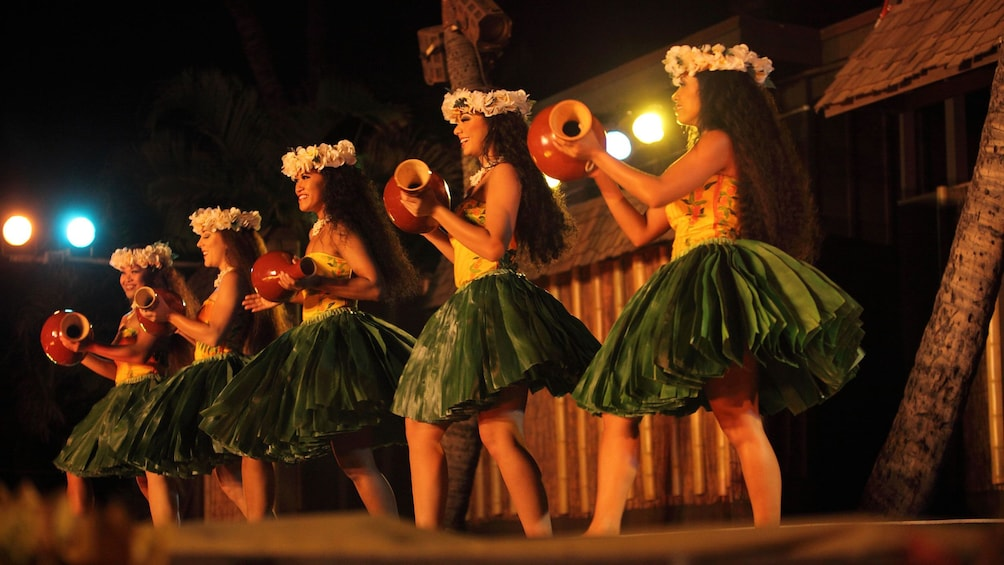 Show item 2 of 8. Luau performers in grass skirts