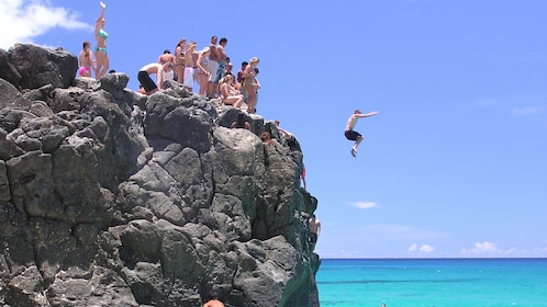 Group cliff jumping into the water on Oahu