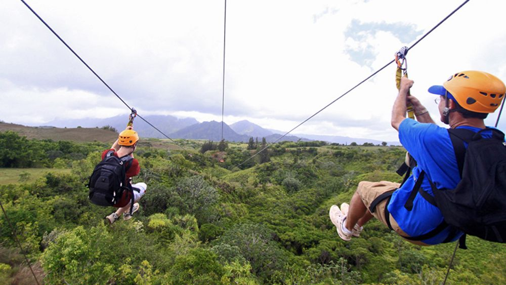 Two people zip lining in tandem