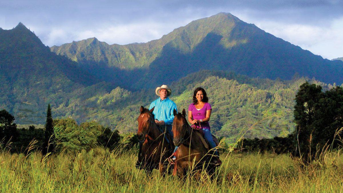 man and woman riding horseback through tall grass in Kauai