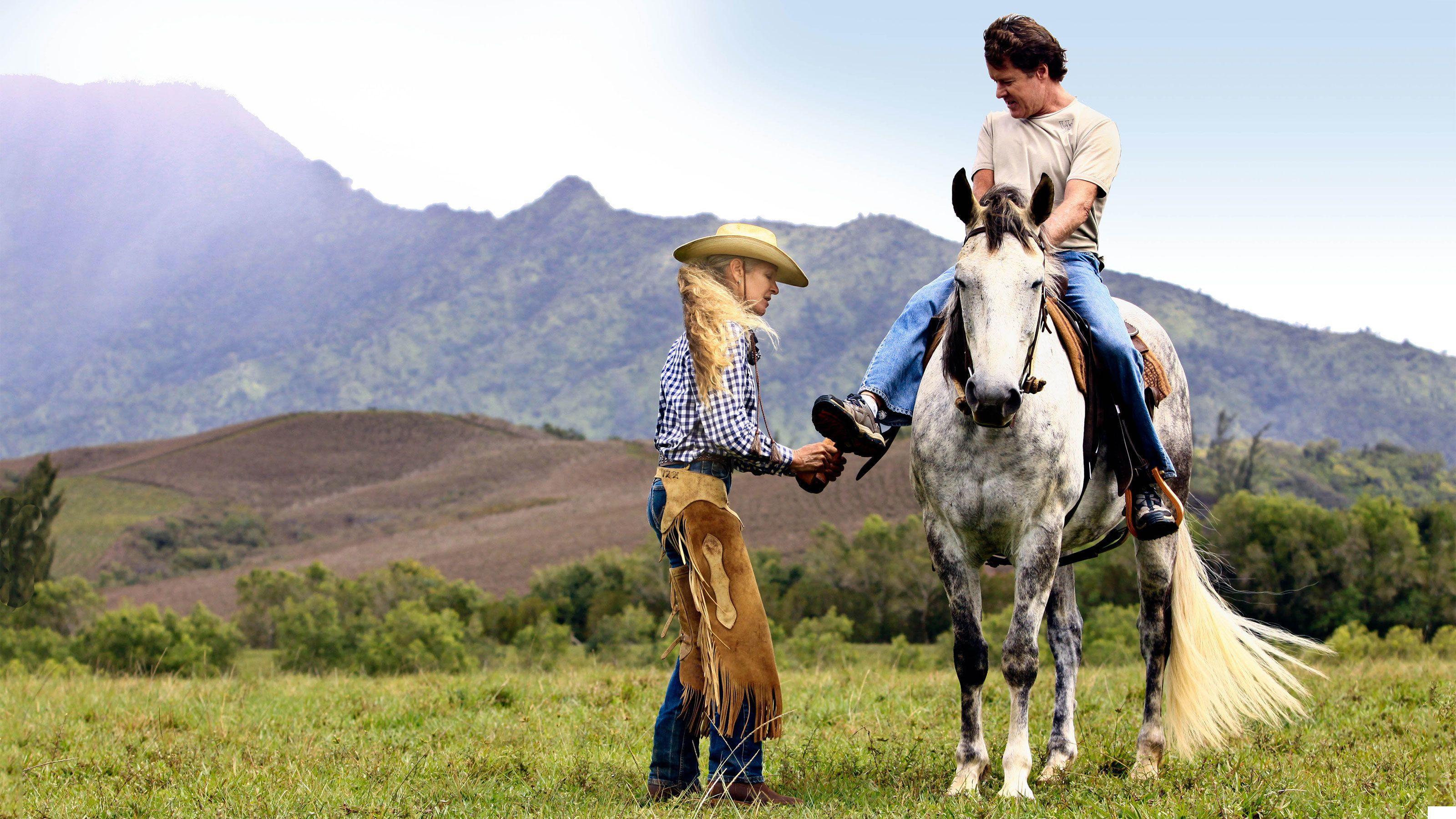 woman adjusting stirrups for man on horse in Kauai