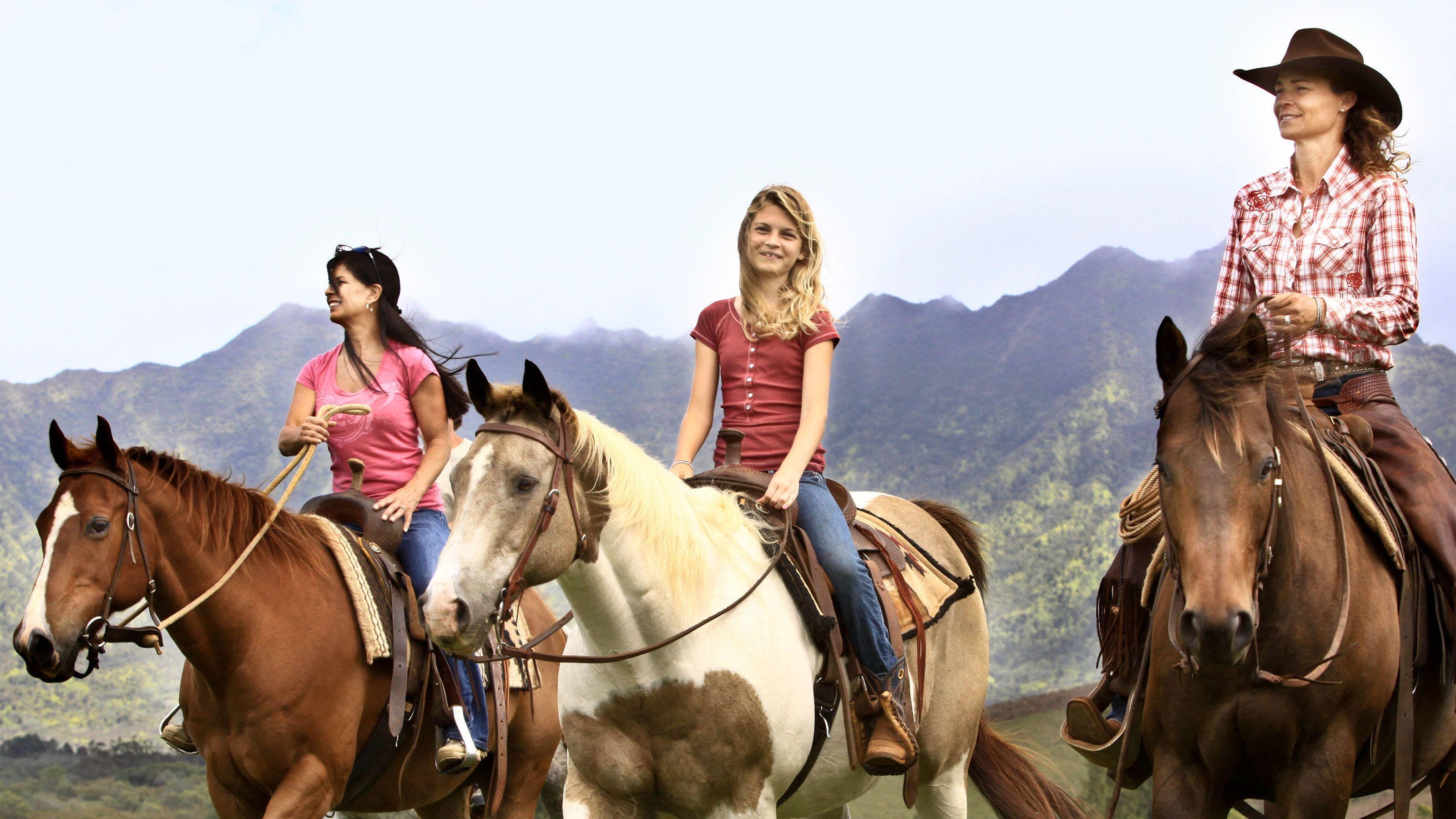 three women riding horseback in Kauai