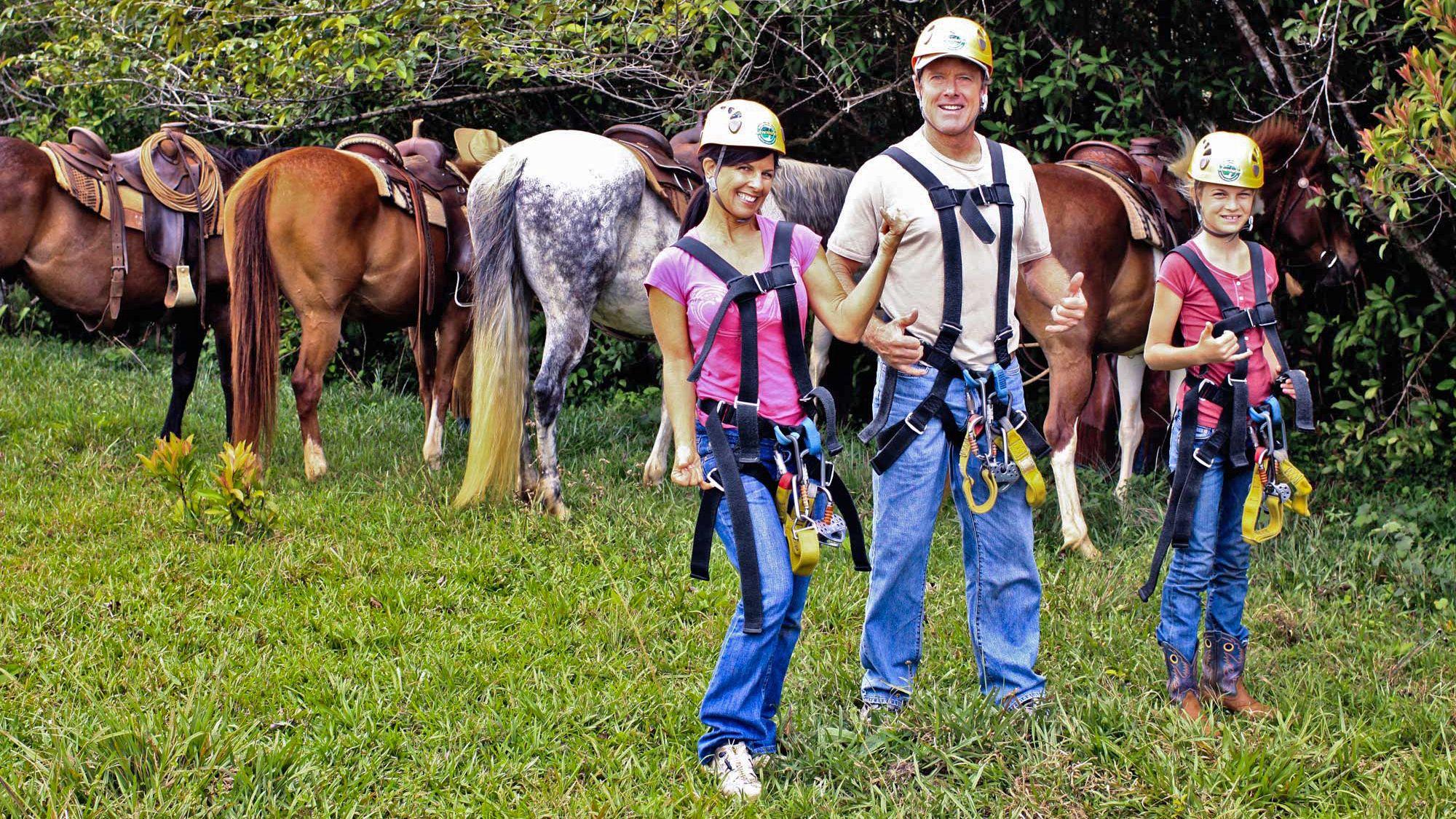 group ready for zip lining near horses in Kauai