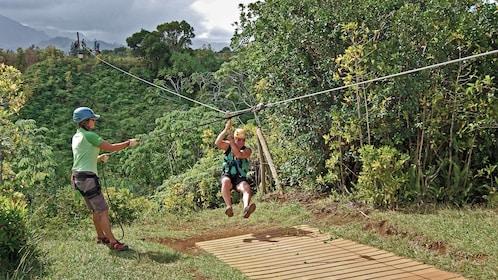 Man at end of zip line rope in Kauai