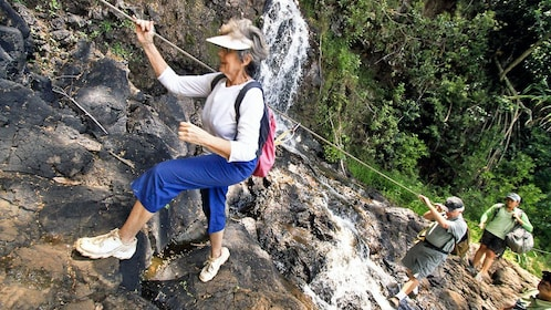 Woman climbing over waterfall using guide rope in Kauai