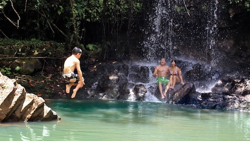 Boy jumping into waterfall pool with parents watching in Kauai